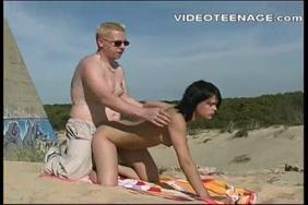 امرأة سمراء لطيف مع حلمات مثقوبة مارس الجنس على الشاطئ.